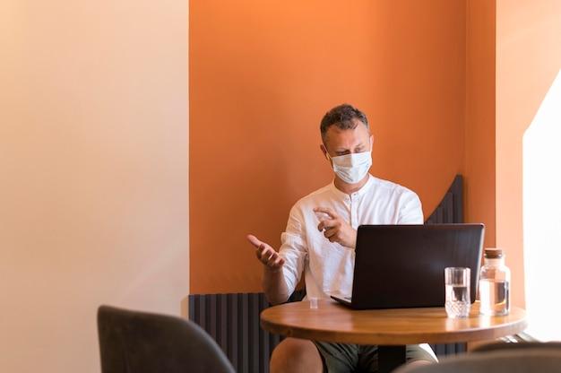 Moderne man aan het werk met zijn medische masker op en zijn handen desinfecterend