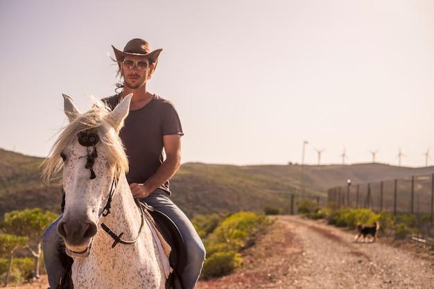 Moderne man cowboy geniet van een natuurlijke en alternatieve levensstijl op een wit paard. vriendschap en natuur buiten voor mooie mensen die een ander leven leiden op het platteland