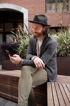 Moderne man die naar muziek luistert op zijn telefoon