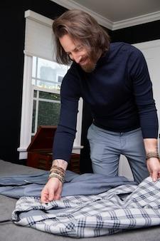 Moderne man die zijn kleren inpakt