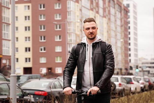 Moderne man elektrische scooter rijden in de stad