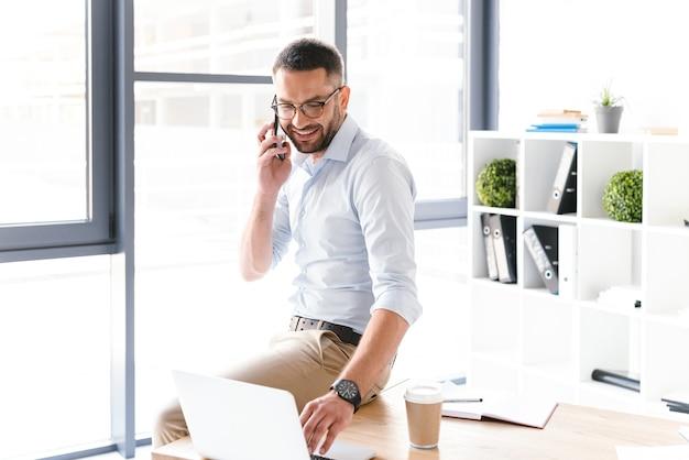 Moderne man in formele slijtage praten over zwarte smartphone over zaken, zittend op tafel in kantoor