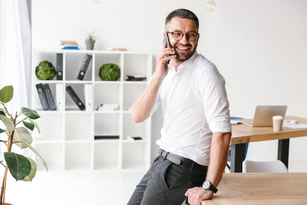 Moderne man in formele slijtage spreken op zwarte smartphone over zaken, zittend op tafel in kantoor