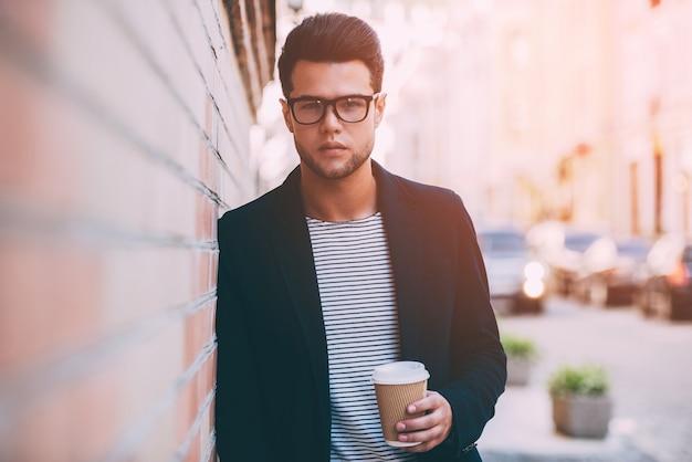 Moderne man. knappe jongeman in slimme vrijetijdskleding met koffiekopje en camera kijkend terwijl hij tegen de bakstenen muur leunt met uitzicht op de stad op de achtergrond