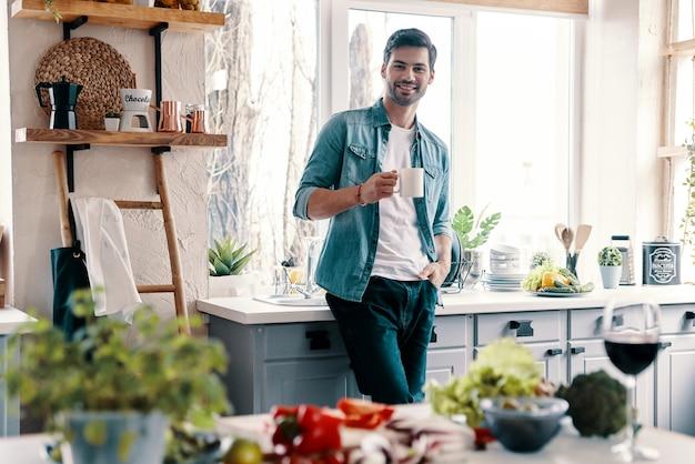 Moderne man. knappe jongeman in vrijetijdskleding die naar de camera kijkt en een warm drankje drinkt terwijl hij thuis in de keuken staat