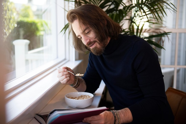 Moderne man leest tijdens het ontbijt