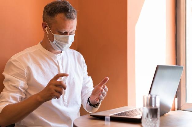 Moderne man met behulp van ontsmettingsmiddel op zijn werk