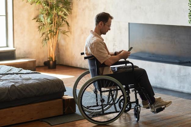 Moderne man met een handicap die smartphone gebruikt