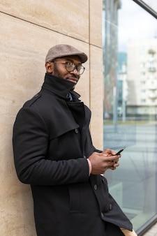 Moderne man met zijn telefoon buitenshuis