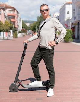Moderne man met zonnebril poseren op scooter