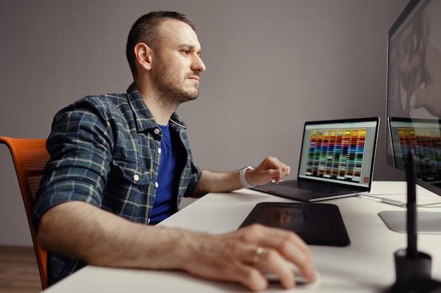 Moderne man op afstand werken op een computer vanuit kantoor aan huis
