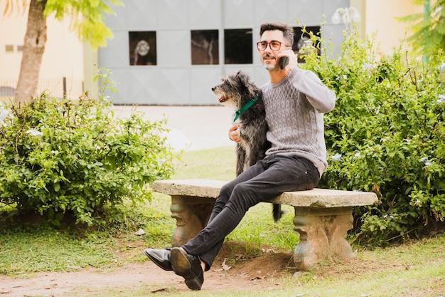 Moderne man zit in het park met zijn hond praten op mobiele telefoon