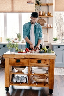 Moderne mannelijkheid. knappe jongeman in vrijetijdskleding die groenten snijdt terwijl hij thuis in de keuken staat