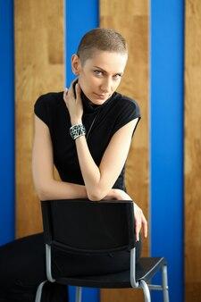 Moderne meisje in een zwarte jurk zit op een stoel op een muur met houten planken.