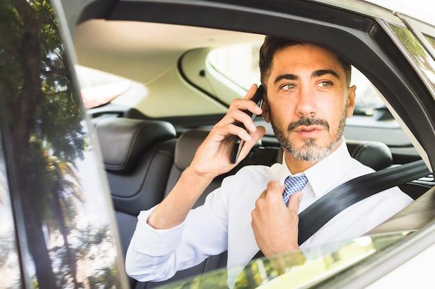 Moderne mens die in de auto zit die zijn halsband aanpast die op mobiele telefoon spreekt