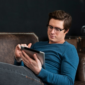 Moderne mens die op zijn tablet kijkt terwijl het blijven in zijn laag