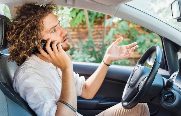 Moderne mens die telefoongesprek in auto maakt
