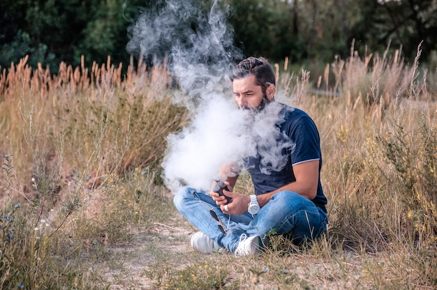 Moderne mens die van een e-sigaret geniet. de mens houdt echt van het roken.
