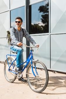 Moderne mens die zonnebril draagt die zijn fiets berijden