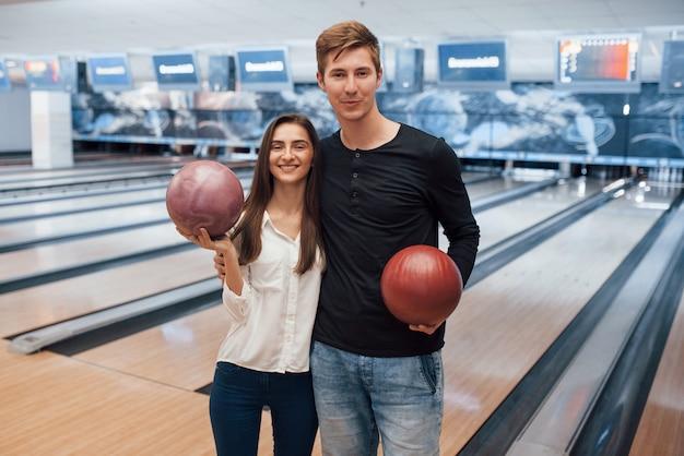 Moderne mensen. jonge, vrolijke vrienden vermaken zich in het weekend in de bowlingclub