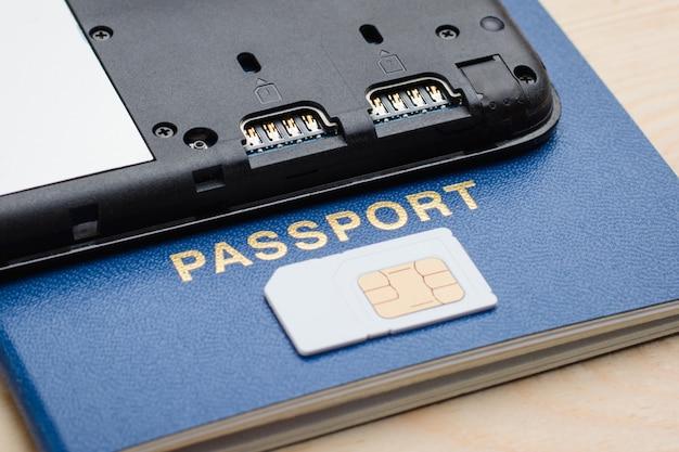 Moderne mobiele telefoon op een paspoort in de buurt van een simkaart. registratie en identificatie sim-kaart voor mobiele telefoon met behulp van paspoort