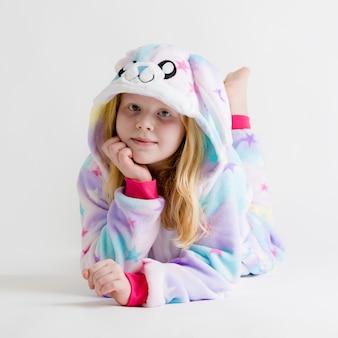 Moderne mode - mooie blonde meisje die zich voordeed op een witte achtergrond in kigurumi-pyjama, konijntjeskostuum