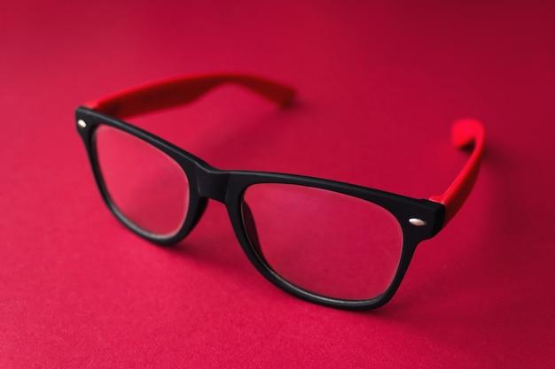 Moderne modieuze afgestudeerd bril op rode achtergrond, bril.