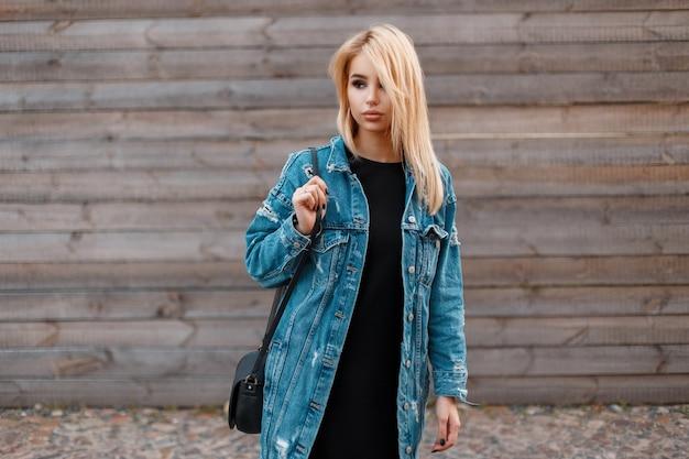 Moderne modieuze jonge blonde vrouw met trendy zwarte handtas in een lange stijlvolle denim jasje in een zwarte jurk staat in de buurt van de houten vintage muur buitenshuis