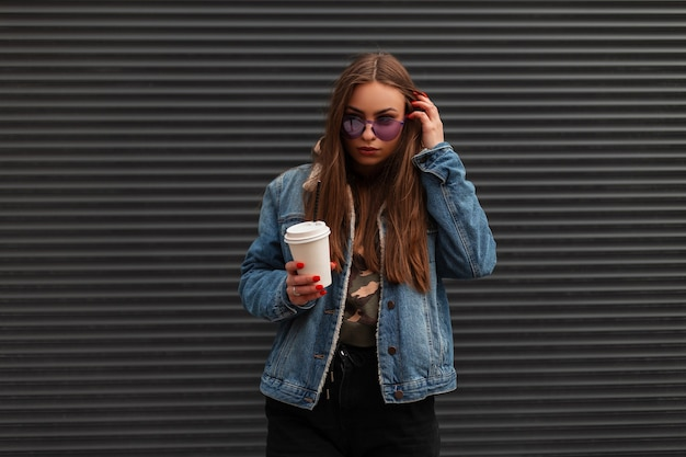 Moderne mooie jonge hipster vrouw in modieuze denim blauwe jas in trendy paarse bril met kop warme koffie staat in de buurt van een grijze muur op straat. trendy mooi meisje poseren in de stad.