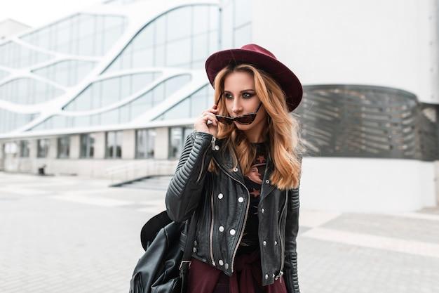 Moderne mooie jonge vrouw hipster in een vintage paarse hoed in een modieus jasje met een leren rugzak met zonnebril