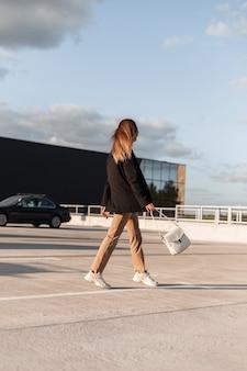 Moderne, mooie stijlvolle vrouw in modieuze zakelijke casual kleding en trendy tas loopt op een buitenparkeerplaats vanuit het winkelcentrum op zonnige zomerdag.