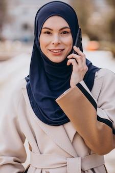 Moderne moslimvrouw die aan de telefoon praat