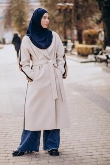 Moderne moslimvrouw die een hoofddoek draagt die op straat loopt