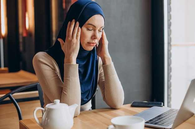 Moderne moslimvrouw die thee drinkt en op de computer werkt in een café