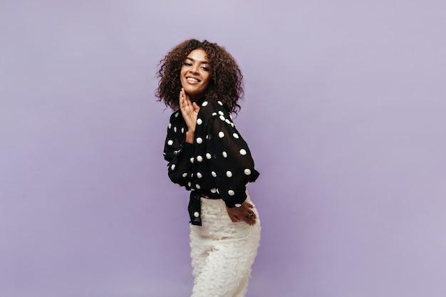 Moderne mulat dame met krullend donkerbruin kapsel in polka dot shirt met lange mouwen en lichte stijlvolle broek glimlachend en kijkend naar de voorkant