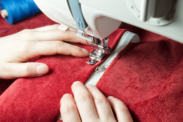 Moderne naaimachine naait op de ritssluiting op rood kledingstuk. naaiproces