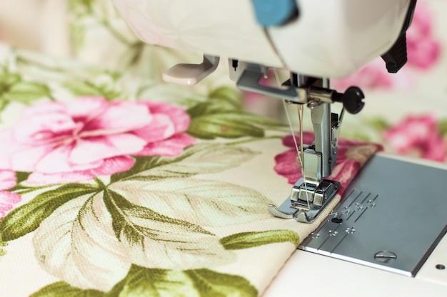 Moderne naaimachine naaivoet maakt een naad op colofrulstof. naaiproces