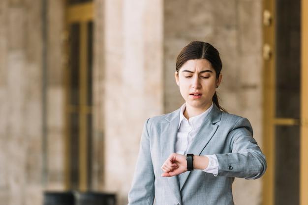 Moderne onderneemster die horloge in openlucht bekijkt