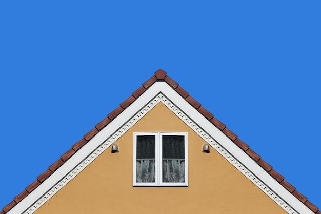 Moderne oranje het ontwerpmuur van het huisgeveltop met duidelijke blauwe hemelachtergrond.
