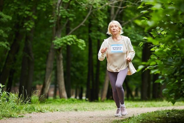 Moderne oude vrouw die sportuitrusting draagt die aan marathonrace in bospark op zomerdag deelneemt