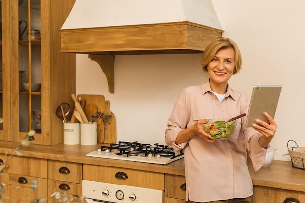 Moderne oudere volwassen vrouw die verse groene salade en groenten eet in de keuken, gelukkig glimlachend. helthy levensstijl concept. tablet gebruiken.