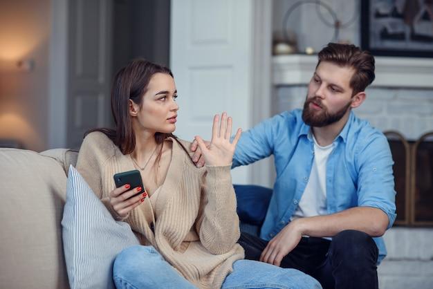 Moderne paar thuis. man en vrouw concentreerden zich op messaging met smartphones, negeerden elkaar en brachten tijd door op sociale media.