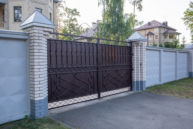 Moderne privé bruine smeedijzeren grote poort van het huis. ideeën voor huisontwerp en decoratie. ijzeren deur voor erfafscheiding. gevel van een huis aan een stadsstraat.