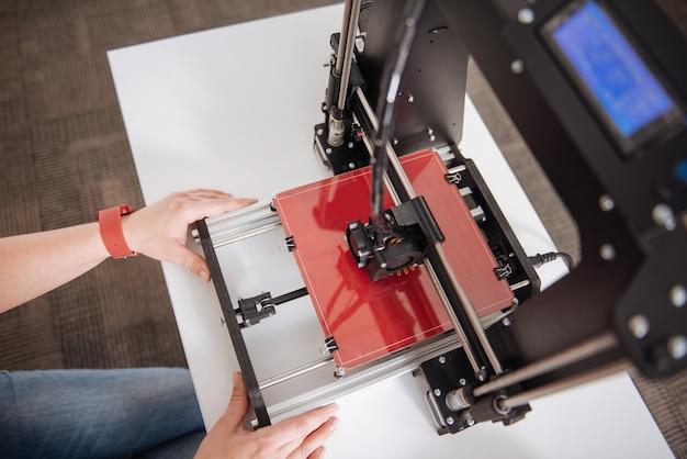 Moderne professionele 3d-printer die wordt gebruikt door een ervaren 3d-ontwerper tijdens het maken van nieuwe objecten