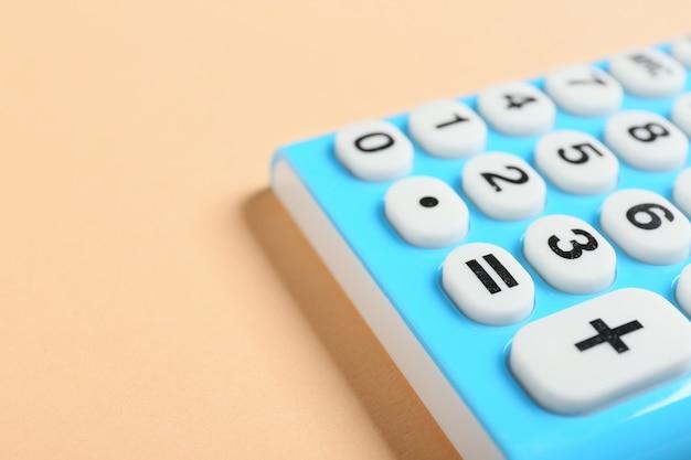 Moderne rekenmachine op kleur oppervlak, close-up