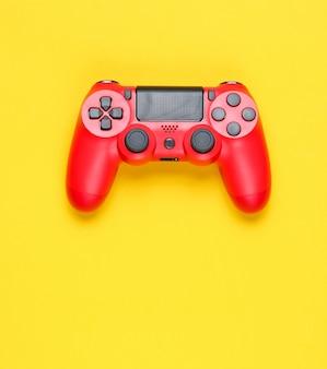 Moderne rode gamepad op een gele achtergrond.