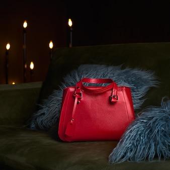 Moderne rode lederen tas voor een zakenvrouw op sofa.