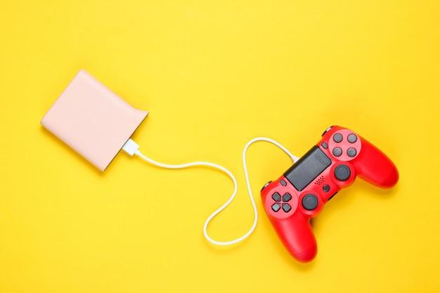 Moderne rode plastic gamepad laadt van powerbank op gele achtergrond.