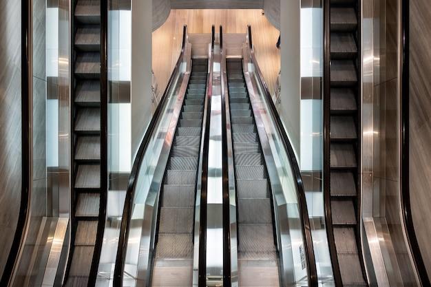 Moderne roltrap die zich parallel in warenhuis beweegt