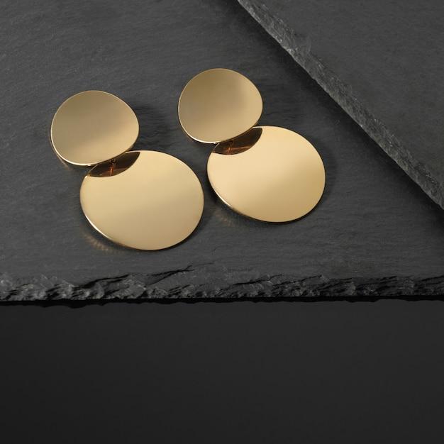 Moderne ronde gouden oorbellen paar op donkere stenen platen